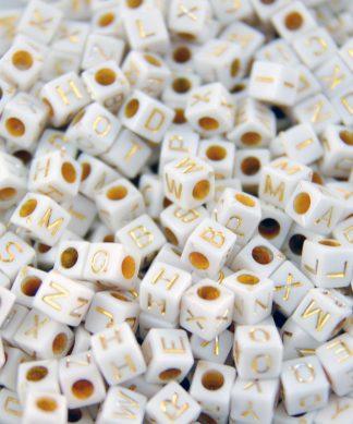 Vita bokstavspärlor med guldbokstäver - kub 100 st